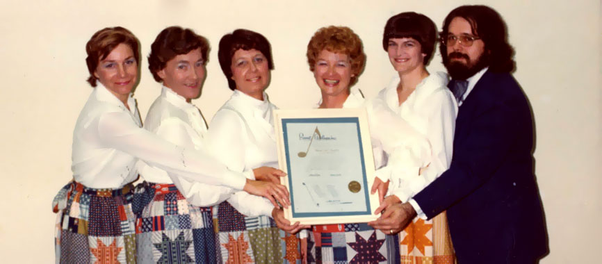 Merrie Dells inaugural members pose with the chorus' Sweet Adelines charter.